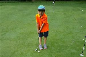 Young boy putting on a golf course.